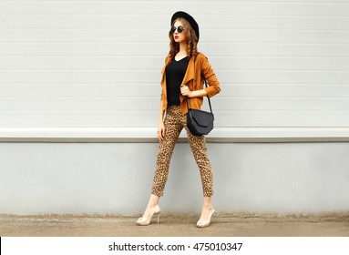 Fashion pretty young woman wearing a retro elegant hat, sunglasses, brown jacket and black handbag walking in city over grey background