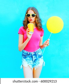 Fashion pretty young woman wearing a t-shirt, denim shorts drinks fruit juice from cup with yellow air balloon over colorful blue background
