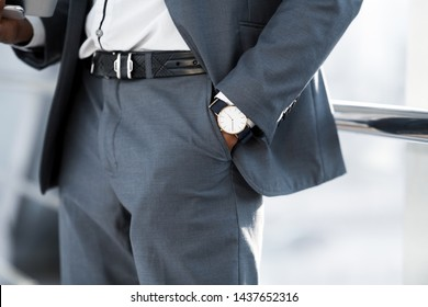 Fashion and Punctuality Concept. Man Hand with Wrist Watch in the Pocket of Stylish Pants
