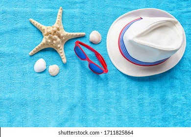 Fashion red glasses, straw hat, starfish, shells on blue beach towel. Concept travel vacation, summer holidays, top view, flat lay. Hipster style.
