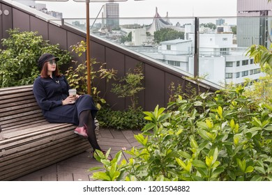 Fashion red hair girl in blue dress, rounded glasses drinking coffee in park-cafe chillout on the roof in big city