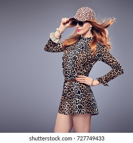 Fashion Redhead Young woman in Sexy Leopard Outfit. Stylish Wavy hairstyle, Sunglasses, Beauty Pretty Woman in Trendy Autumn Jumpsuit, Glamour Cap. Playful Model Girl Luxury