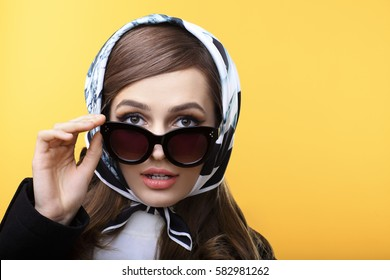 Fashion retro style portrait of beautiful surprised woman in sunglasses on yellow background with copy space
