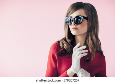 Fashion retro style portrait of young beautiful woman in sunglasses on pink background with copy space