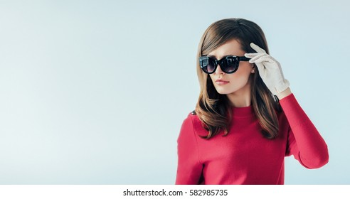 Fashion retro style portrait of young beautiful woman in sunglasses on white background with copy space