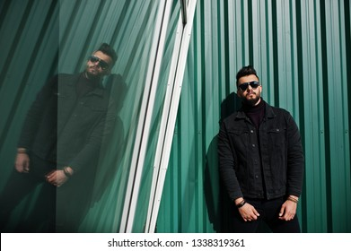 Fashion rich beard Arab man wear on black jeans jacket and sunglasses posed against green wall with windows. Stylish, succesful and fashionable arabian model guy.