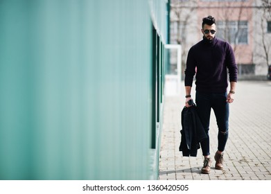 Fashion rich beard Arab man wear on turtle neck and sunglasses walking against green wall with jacket on hand. Stylish, succesful and fashionable arabian model guy.