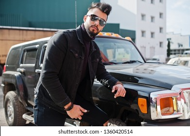 Fashion rich beard Arab man wear on black jeans jacket and sunglasses posed against big black suv car. Stylish, succesful and fashionable arabian model guy.