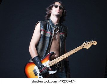 fashion rock guitarist playing electric guitar isolated on black background