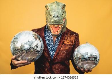 Fashion senior man wearing t-rex dinosaur mask while celebrating carnival holidays - Surreal masking concept
