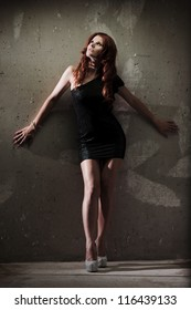 Fashion sensual portrait of young sexy redhead girl over grunge wall