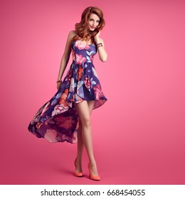 Fashion Sensual Slim Redhead Woman Smiling. Beauty Model in Summer Outfit. Trendy Floral Dress, Stylish Curly Wavy hairstyle, Luxury Heels. Playful Romantic fashionable Lady on Pink.