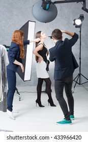 Fashion session in a photographic studio, with a model in a black and white dress, a photographer and his assistant