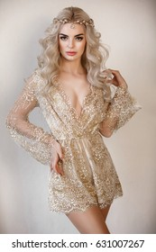 Fashion sexy blond woman in boudoir lace dress with jewelry. Portrait of sensual beautiful bride boho style. Beauty lady with wedding hairstyle long curly blond hair and bridal makeup. Vintage lady.