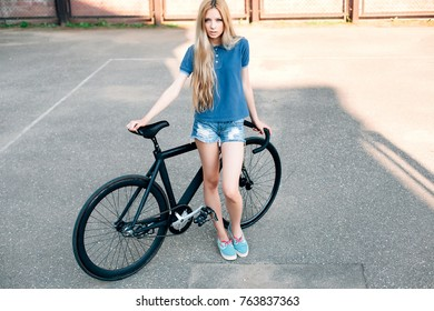Fashion sexy blonde beautiful woman posing on the street in hot summer day with sport fixed gear bicycle