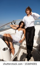 Fashion sexy couple posing on the luxury boat in open sea in summer. Young man and sensual brunette outdoor portrait in classic dress near the ocean. Outdoors, lifestyle.