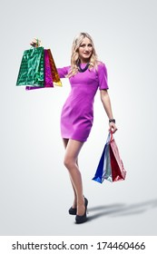Fashion Sexy Girl in dress, full length Portrait. Woman with Shopping Bags. Shopper. Sales. Studio shooting
