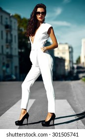 Fashion sexy hot businesswoman girl model in white suit in sunglasses in the street
