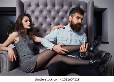 Fashion of sexy lovers, pretty brunette woman and bearded man, on Valentine's day. Love. Flirt. Young couple of pretty sexy woman in gray dress has slim body and handsome man with long beard in shirt.
