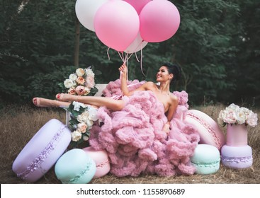 Fashion sexy woman dressed in pink stunning dress, surrounded decorations of big French Macarons and balloons and fresh flowers. Holiday or birthday party for your lady