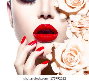Fashion Sexy Woman with flowers. Vogue style Model girl face with roses. Red Sexy Lips and Nails closeup. Manicure and Makeup. Make up. Beauty lady face isolated on white background. Perfect skin