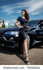 Fashion sexy woman in luxury black car posing outdoors. Glamour model with red lips and retro hairstyle curls in sport car st street. Vogue style girl in black dress with bright makeup and automobile.