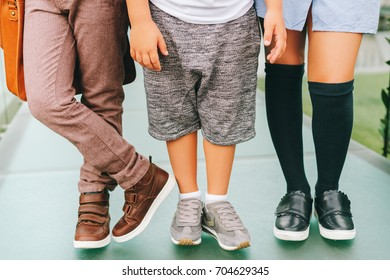 Fashion shoes on kids. Three pairs of children's feet wearing comfortable and fashion trainers. Back to school concept