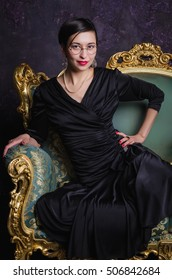 Fashion shoot of beautiful asian woman in a long black dress sitting on classic sofa. Girl looks at camera.