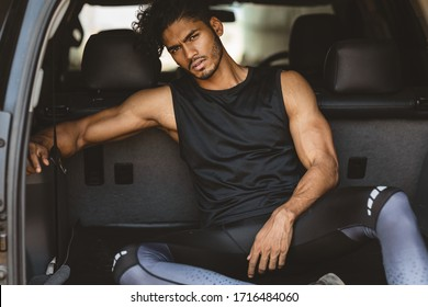 Fashion shoot of a handsome and sexy indian or arab looking male fitness model with a gym fit body and black curly hair and a stylish small beard sitting and posing in the back of a car