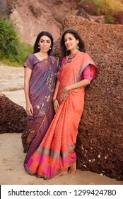 Fashion shoot of indian woman in traditional clothes. Friends girl in beautiful saree standing on the rock near the sea in saree at sunset