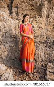 Fashion shoot of indian woman in traditional clothes. Woman in beautiful saree standing on the rock near the beach