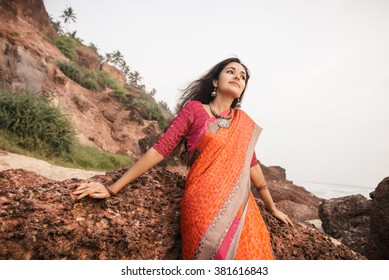 Fashion shoot of indian woman in traditional clothes. Woman in beautiful saree sitting on the rock near the beach