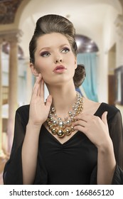 fashion shoot of pretty young brunette girl with elegant style, beautiful hair-style, black dress and big necklace