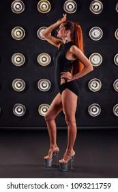 Fashion shoot of a sexy striptease dancer in studio.