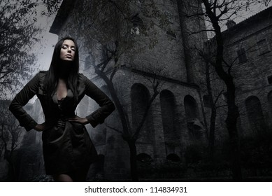 Fashion shoot of young and sexy brunette over the ancient building background