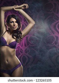 Fashion shoot of young sexy woman in lingerie over the smoky background