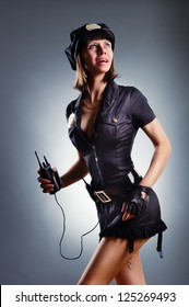 Fashion shoot of young sexy woman in clothes policeman with a radio in her hand