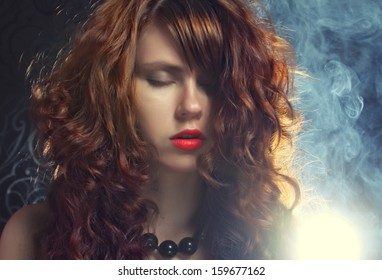 Fashion shoot of young and sexy woman in smoke