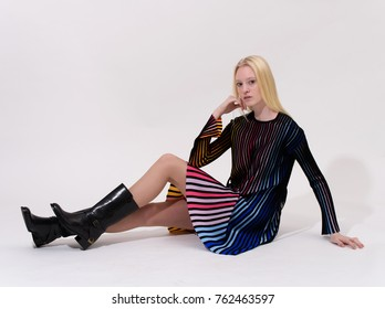 Fashion shooting in studio . Professional model of blonde in colored dress , fashionable clothes and style, new collection. stylish look.
