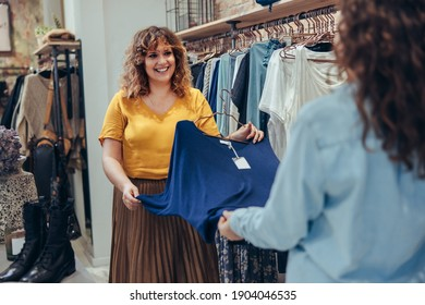 Fashion shop clerk helping female customer in choosing clothes in store. Saleswoman assisting client in clothing store.