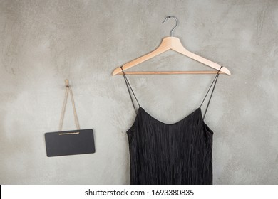 Fashion and shopping concept - blank blackboard and beautiful little black dress on a hanger on grey background
