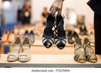 Fashion shopping footwear store  : woman holding shoes in her hands for choose and shopping looking at the shelves with numerous footwear. Display Shelf in Shoe shop.