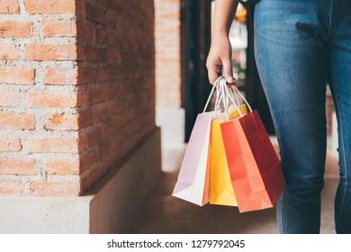 Fashion shopping girl, Young woman carrying colorful shopping bags while walking along the shopping mall.