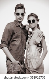 Fashion shot of an attractive young couple in jeans clothes posing outdoor. Toned photo, sepia.