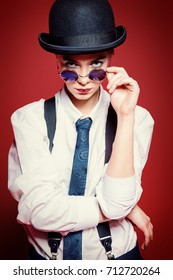 Fashion shot. Attractive young woman posing in a man's clothes and bowler hat. Man's style clothing. Red background.