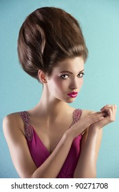 fashion shot of a beautiful brunette with a couture hair style wearing a pink evening dress