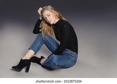 Fashion shot. Beautiful female model posing at studio in casual jeans and boots. Youth style.