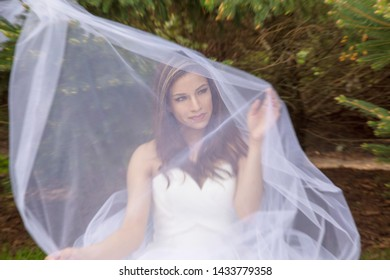 fashion shot of beautiful latina woman outside in white dress behind tulle
