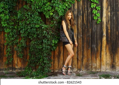 Fashion shot of a beautiful model posing at the vineyard wall