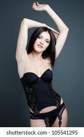 Fashion shot of a beautiful sexy girl in a black underwear. Posing in studio
